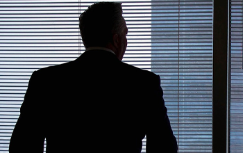 A man in a suit looking out the blinds